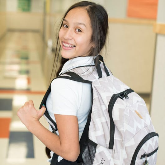 Female student smiling with backpack on.